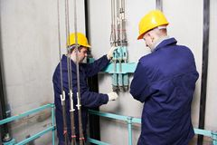 Machinists adjusting lift in elevator hoistway Royalty Free Stock Image