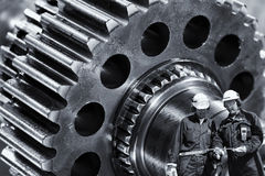 Machinists, engineers with giant cogwheels machinery. Two machine-workers, engineers with giant cogwheels machinery in background, oily gears and cogs Royalty Free Stock Photo