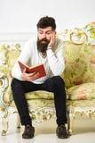 Machista en el libro de lectura agujereado de la cara Concepto de la literatura científica El hombre con la barba y el bigote se  fotos de archivo