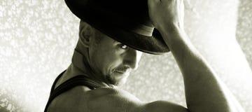 Machista muscular en un sombrero de fieltro Imágenes de archivo libres de regalías