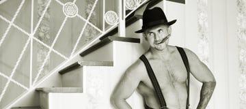 Machista muscular en un sombrero de fieltro Imagenes de archivo