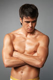 Macho. Naked muscular young man isolated on gray Stock Image