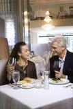 Macho adulto e fêmea que sentam-se na tabela do restaurante. Imagens de Stock Royalty Free