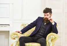 Macho attractive and elegant on serious face and thoughtful expression. Elite lifestyle concept. Man with beard and. Mustache wearing classic suit, sits on old stock photos