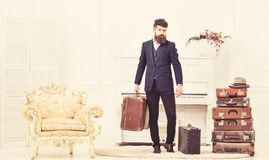 Macho attractive, elegant on strict face carries vintage suitcases. Man with beard and mustache wearing classic suit. Delivers luggage, luxury white interior royalty free stock photography