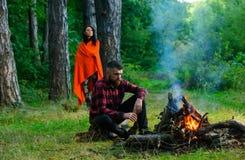 Macho avec de la bière se reposant près du feu, vacances avec l'épouse Image libre de droits