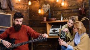 Macho avec le visage brutal tenant la guitare électrique Homme barbu jouant l'instrument de musique Homme avec la barbe de hippie Photographie stock libre de droits