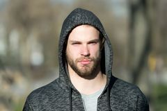 Macho with beard in hood on sunny day. Bearded man wear casual sweatshirt outdoor. Fashion guy in stylish sportswear. Lifestyle fo stock image