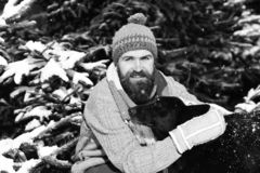 Macho with beard and mustache hugs dog. Man wears knitted hat, scarf and gloves with black dog.Guy with smiling face with firtrees covered with snow on stock images