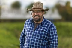Macho brutal dans l'ulybayutsya de chapeau de cowboy et la vie heureuse, pleins barbus de la positivité et de l'optimisme Photographie stock libre de droits