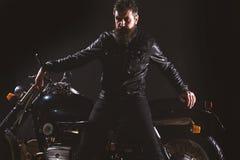 Macho, brutalny rowerzysta w skórzana kurtka stojaku blisko motocyklu przy nighttime, kopii przestrzeń Mężczyzna z brodą, rowerzy obraz royalty free