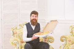 Macho in classic clothes hungry and excited holds cheese pizza, eats, enjoying aroma, interior background. Man with. Beard and mustache holds box with tasty royalty free stock photography