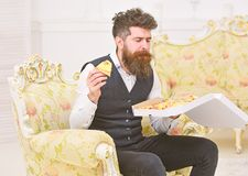 Macho in classic clothes hungry, holds slice of cheese pizza, eats, enjoying taste, interior background. Man with beard. And mustache holds box with tasty fresh stock image
