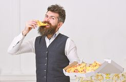 Macho in classic clothes hungry, holds slice of cheese pizza, eats, white background. Man with beard and mustache holds. Delivered box with tasty fresh hot royalty free stock photos