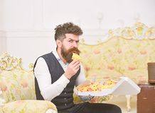 Macho in classic clothes hungry, on strict face, holds slice of pizza, eats, interior background. Man with beard and. Mustache holds delivered box with tasty royalty free stock photography