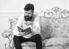 Macho on concentrated face reading book. Scandalous bestseller concept. Guy reading book with attention. Man with beard. And mustache sits on baroque style sofa stock images