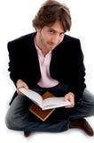 Macho de assento considerável com livros Fotografia de Stock