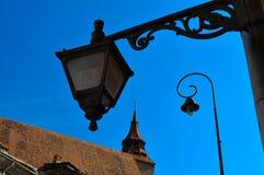 Macho de oro del festival del centro de la lámpara de calle de la iglesia negra de Brasov Rumania de la ciudad vieja europea de T fotos de archivo libres de regalías