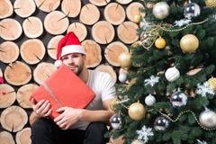 Macho in de rode gift van de hoedengreep op houten logboeken Stock Afbeeldingen