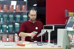 Macho do assistente de loja que faz a varredura de um livro Imagens de Stock