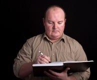 Macho do excesso de peso com livro preto e pena Fotos de Stock Royalty Free