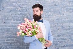 Macho dostaje gotowa romantyczna data Tulipany dla Ona Obs?uguje dobrze przygotowywaj?cego smokingu ??ku krawata chwyta kwiat?w b obrazy royalty free