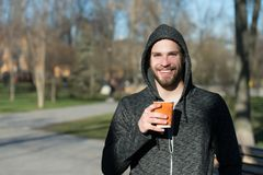 Macho felice in tazza di caffè eliminabile della tenuta del cappuccio in parco soleggiato Sorriso barbuto dell'uomo con la bevand fotografie stock libere da diritti