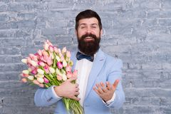 Macho getting ready romantic date. Tulips for sweetheart. Romantic gift. Man well groomed tuxedo bow tie hold flowers. Bouquet. How to be gentleman. Guide for royalty free stock photography