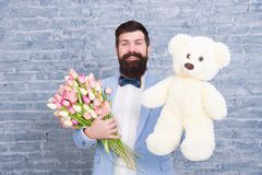 Macho getting ready romantic date. Waiting for darling. Man well groomed wear tuxedo bow tie hold flowers tulips bouquet. And big teddy bear toy. Invite her stock photo