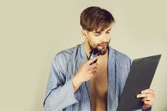 Macho looking at mirror and shaving beard with shaver. Macho or handsome man with blond hair in blue robe looking at mirror and shaving beard with electric royalty free stock images