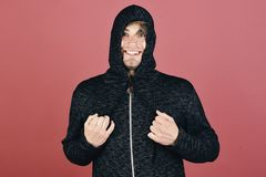 Macho with happy smiling face ties hood tightly. Guy with bristle in dark grey and black hoodie. Sports fashion and fun concept. Man with head covered all over stock photos
