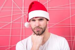 Macho i skägg för santa hatthandlag på allvarlig framsida Arkivbild
