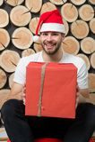 Macho im roten Hutlächeln mit Geschenk Stockbild