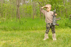 Macho little boy playing with a gun Royalty Free Stock Image