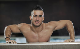 Macho man. Young healthy good looking macho man model athlete at hotel indoor pool Stock Image