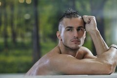 Macho man. Young healthy good looking macho man model athlete at hotel indoor pool Stock Photos