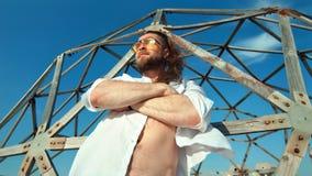 Macho man för stiligt skäggigt lopp som poserar nära raster på för strandbakgrund för blå himmel som att koppla av är utomhus- lager videofilmer