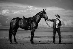 Macho man handsome cowboy and horse on the background of sky and water. Macho man handsome cowboy with amazing muscles and abs and horse are on the background stock image