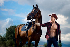 Macho man handsome cowboy and horse on the background of sky and water. Macho man handsome cowboy with amazing muscles and abs and horse are on the background royalty free stock image