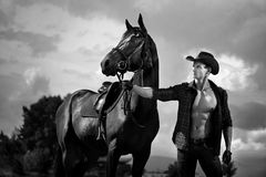 Macho man handsome cowboy and horse on the background of sky and water. Macho man handsome cowboy with amazing muscles and abs and horse are on the background royalty free stock photo