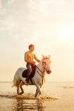 Macho man and horse on the background of sky and water. Boy mode Stock Photo