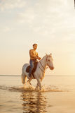 Macho man and horse on the background of sky and water. Boy mode Stock Photos