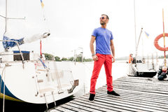 Macho man posing at seaport against yachts Stock Photography