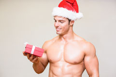 Macho man in santa hat holding gift over white background Stock Photography