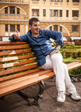 Macho man sitting on bench Royalty Free Stock Photo