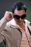 Macho man taking off sunglasses. Macho looking man taking off his sunglasses Royalty Free Stock Images