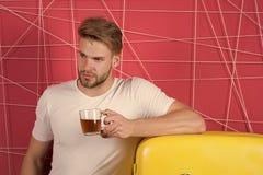 Macho med råna av funderat vin på kylen Ungkarl med morgondrinken på kylskåpet Manhållkopp te eller kaffe in arkivbilder