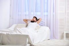 Macho med skägghållhänder bak huvudet som kopplar av Mannen i skjorta som lägger på säng, vit hänger upp gardiner på bakgrund Myc Royaltyfri Foto
