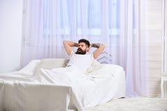 Macho med skägghållhänder bak huvudet som kopplar av Mannen i skjorta som lägger på säng, vit hänger upp gardiner på bakgrund Gra Royaltyfria Foton