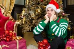 Macho mit ernstem Gesicht in Sankt-Hut bereiten Geschenkboxen vor Lizenzfreies Stockbild